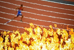 The fumes of the Olympic Flame distort a runner competing in the 400m portion of the Men's Decathlon Wednesday, Aug. 8, 2012 at the Olympic Stadium. The flame could only be viewed by those fortunate enough to get tickets to Track and Field.