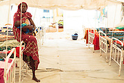 A woman holds her child, who is recovering from malnutrition, as she sits on the end of a bed in a tent at a UNICEF-sponsored therapeutic feeding center at the Mongo hospital in the town of Mongo, Guera province, Chad on Tuesday October 16, 2012.