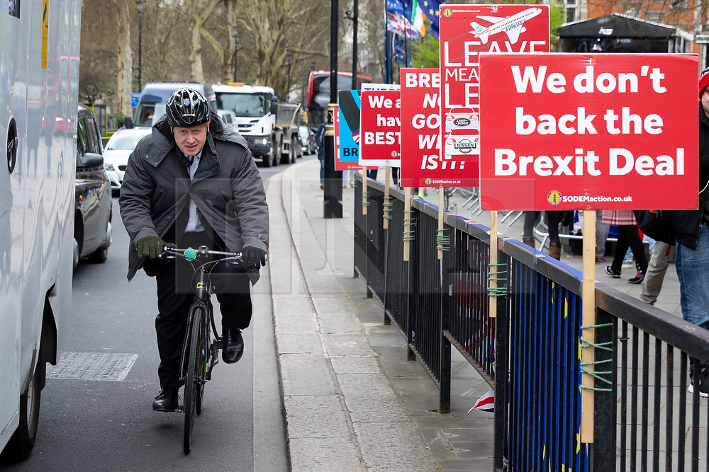 © Licensed to London News Pictures. 27/03/2019. London, UK. Boris Johnson MP passes anti-Brexit placards in Westminster ahead of Prime Minister's Questions. Later today MPs are expected to vote on a series of indicative votes on alternative proposals to British Prime Minister Theresa May's withdrawal agreement. Photo credit : Tom Nicholson/LNP