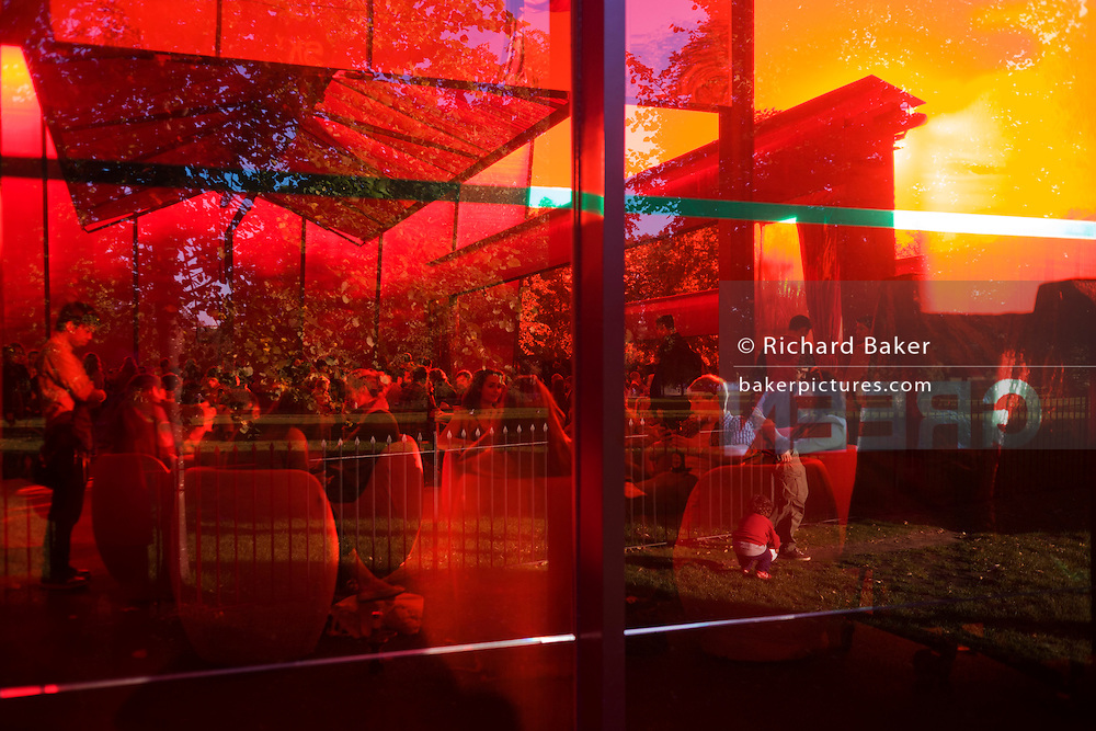 Red-tinted window landscape caused by the Serpentine Gallery's Pavillion.