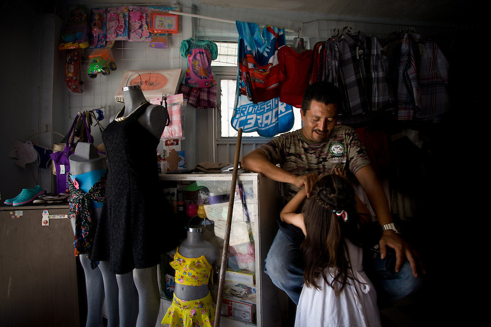 Rene Varela (40), a community police volunteer, at this shop with his youngest daughter. Rene and his family have lived through four kidnappings, including his own experience. He now gives a large part of his time to the community police to prevent crime. His wife is not happy with his frequent absence and does not understand why he would want to risk his life because she doesn't know that her husband was kidnapped.