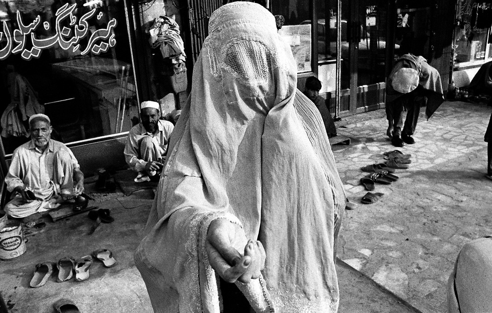 An Afghan woman, a refugee who fled the conflict in her homeland,  begs for small change on Cinema Road Old City Peshawar Pakistan....