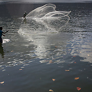 Men cast their nets while fishing in the Lagoa Rodrigo de Freitas behind Leblon and Ipanema beach, Rio de Janeiro,  Brazil. 7th August 2010. Photo Tim Clayton.