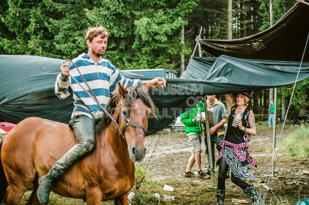 A man rides a horse bareback through the campsite, Czech Republic, 'Summer of Hate', July 2010