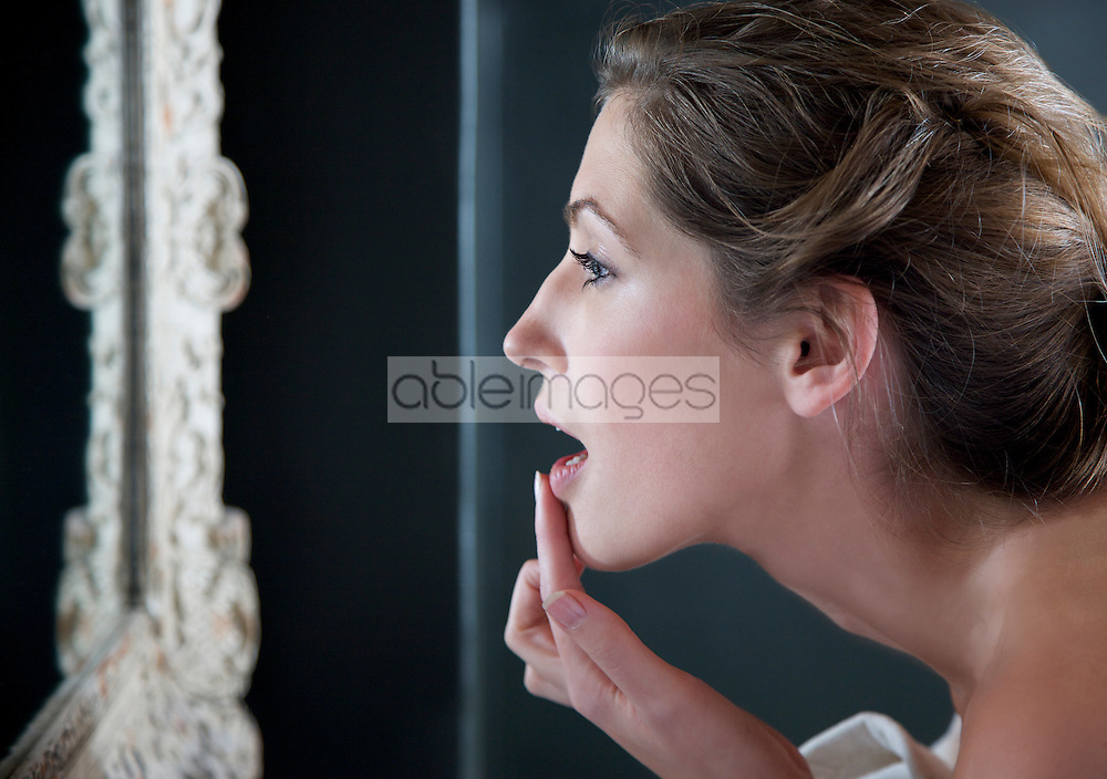 Profile of a woman looking into the mirror touching her lips with her fingers - close up