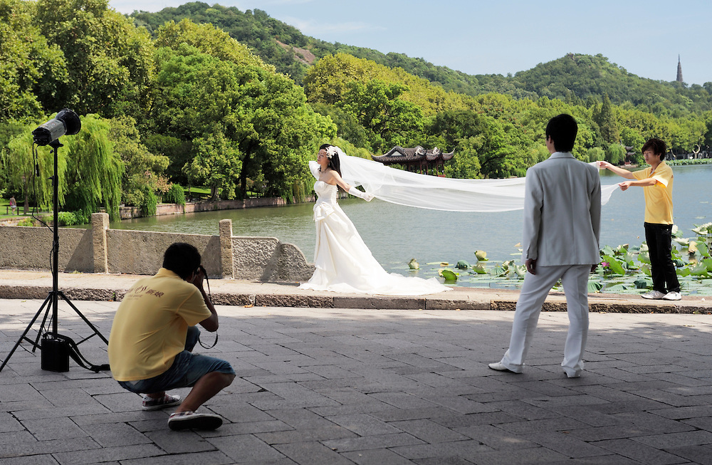 Hangzhou, Zhejiang, China.  Taking wedding photographs on the scenic shores of West Lake in the city of Hangzhou