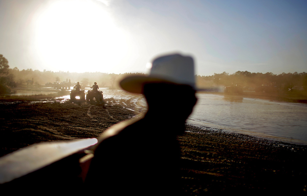 Revelers on four wheelers drive around the Redneck Yacht Club in Punta Gorda, Fla. Photo by: Greg Kahn