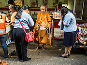 14 DECEMBER 2015 - BANGKOK, THAILAND: A Buddhist monk collects alms in Bang Chak Market. The market closes permanently on Dec 31, 2015. The Bang Chak Market serves the community around Sois 91-97 on Sukhumvit Road in the Bangkok suburbs. About half of the market has been torn down. Bangkok city authorities put up notices in late November that the market would be closed by January 1, 2016 and redevelopment would start shortly after that. Market vendors said condominiums are being built on the land.       PHOTO BY JACK KURTZ