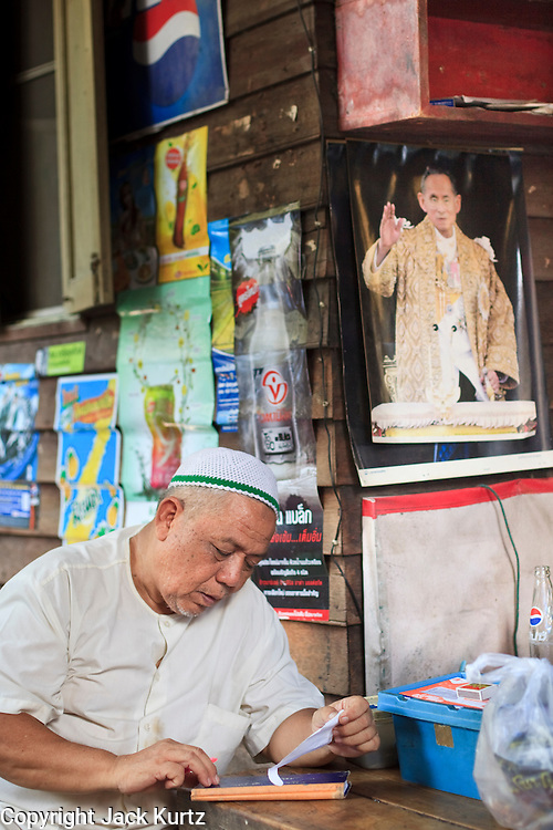"Mar 23, 2009 -- BANGKOK, THAILAND: A Moslem storekeeper balances his books in his shop in Ban Krua. The Ban Krua neighborhood of Bangkok is the oldest Muslim community in Bangkok. Ban Krua was originally settled by Cham Muslims from Cambodia and Vietnam who fought on the side of the Thai King Rama I. They were given a royal grant of land east of what was then the Thai capitol at the end of the 18th century in return for their military service. The Cham Muslims were originally weavers and what is known as ""Thai Silk"" was developed by the people in Ban Krua. Several families in the neighborhood still weave in their homes.     Photo by Jack Kurtz"