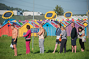 Queueing for the eco friendly showers in front of Solar powered huts, part of the greening of Glastonbury - The 2019 Glastonbury Festival, Worthy Farm. Glastonbury, 27 June 2019