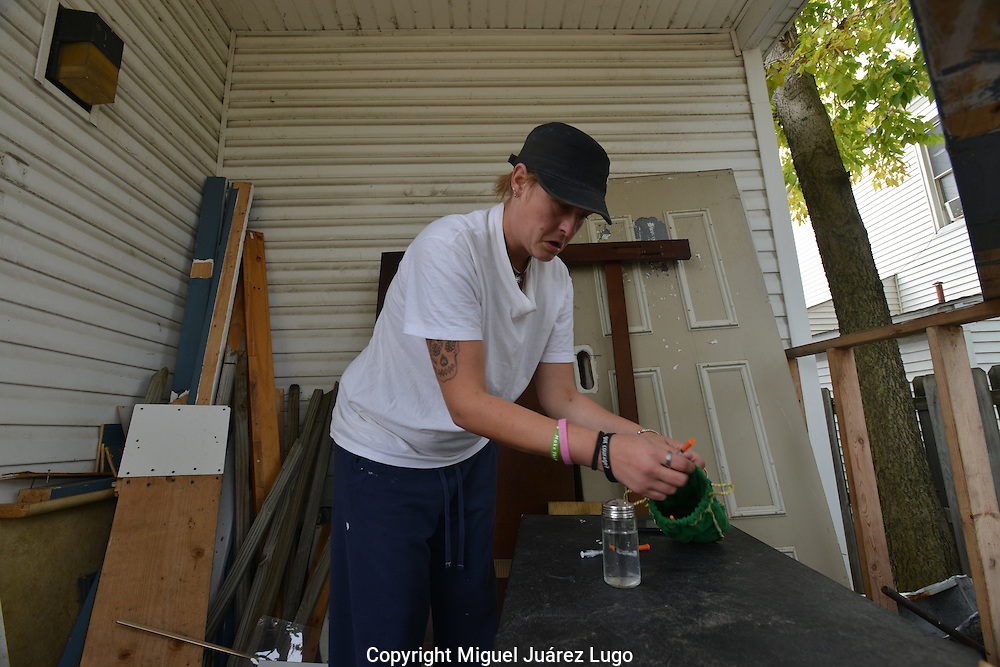 "Krystal Hatfield, 28, a heroin addict, prepares to shoot her morning fix on the back porch of an abandoned house in Hamilton, Ohio, an epicenter of a growing heroin epidemic across the U.S. A mother of two--she had her first child at 14, the second at 16--she says she uses drugs in part to cover the pain of her childhood, when she was molested by a cousin from the age of 4 to 11, and had a crack addicted mother and an alcoholic father. She makes money by performing phone sex for an old truck driver--her ""sugar daddy,"" she says--who pays her $30 per session via Western Union."