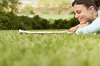Woman lying on grass reading newspaper side view.