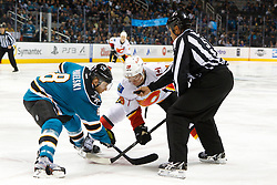 Feb 8, 2012; San Jose, CA, USA; NHL linesman Jay Sharrers (57) drops the puck on a face off to San Jose Sharks center Joe Pavelski (8) and Calgary Flames center Blair Jones (19) during the second period at HP Pavilion. Calgary defeated San Jose 4-3. Mandatory Credit: Jason O. Watson-US PRESSWIRE