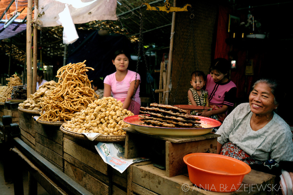 Burma/Myanmar, Bagan. Women selling snack in the market near Ananda Temple.