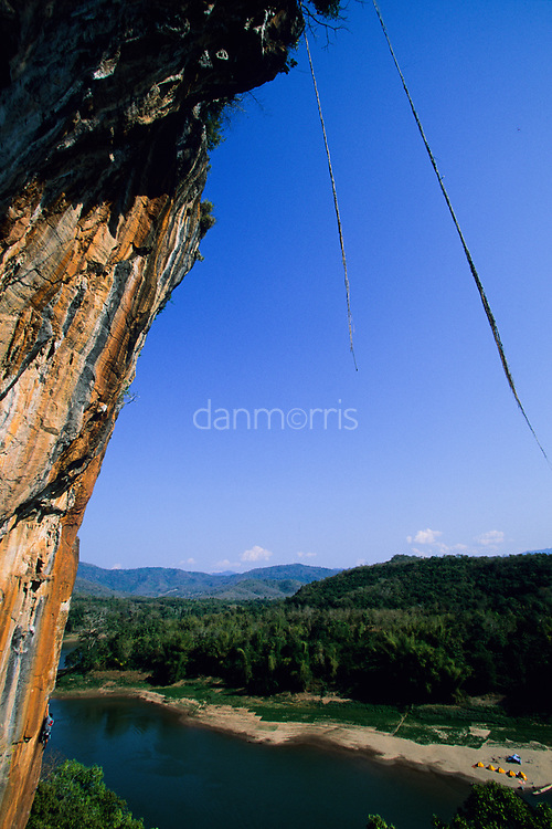 Tamotsu Sugino climbs the orange arete Mind the Bees, 5.13a,  over the Nam Ou River, Ban Pak Ou, Luang Phrabang, Laos