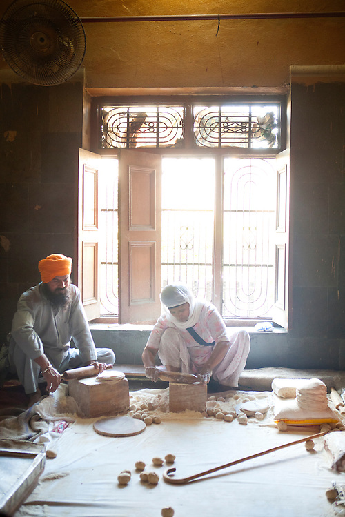 a man and a woman volunteer to make chapati in the golden temple, Amritsar India. There are hundreds of volunteers at the golden temple that help produce tens of thousands of free meals everyday!