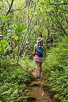 Woman walking with a walking staff through a tropical forest on the Na Pali Coast of Kauai, Hawaii.