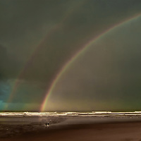 "This double rainbow appeared on a very stormy day along the west coast. The few folks on the beach were ""braving"" it. The dark sky with a touch of blue was compelling."