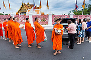 "21 JULY 2013 - BANGKOK, THAILAND:  People present monks with alms and make merit at Wat Benchamabophit on the first day of Vassa, the three-month annual retreat observed by Theravada monks and nuns. On the first day of Vassa (or Buddhist Lent) many Buddhists visit their temples to ""make merit."" During Vassa, monks and nuns remain inside monasteries and temple grounds, devoting their time to intensive meditation and study. Laypeople support the monastic sangha by bringing food, candles and other offerings to temples. Laypeople also often observe Vassa by giving up something, such as smoking or eating meat. For this reason, westerners sometimes call Vassa the ""Buddhist Lent.""       PHOTO BY JACK KURTZ"