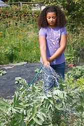Girl watering broad bean plants with hosepipe