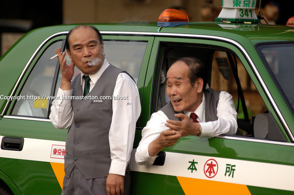 Two taxi drivers taking a break and chatting in Tokyo