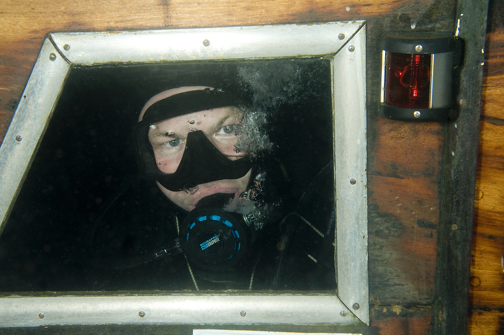 Diver inside the wreck of a sunken boat. Location : Stavanger, Norway
