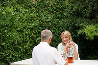 Couple drinking wine sitting at outdoor table