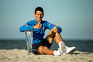 Miami, FL - Novak Djokovic of Serbia poses with the championship trophy in Key Biscayne after defeating Andy Murray of Great Britain on day 14 of the Miami Open 2015.