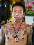 """07 MARCH 2015 - NAKHON CHAI SI, NAKHON PATHOM, THAILAND: A tattooed man at the Wat Bang Phra tattoo festival. Wat Bang Phra is the best known """"Sak Yant"""" tattoo temple in Thailand. It's located in Nakhon Pathom province, about 40 miles from Bangkok. The tattoos are given with hollow stainless steel needles and are thought to possess magical powers of protection. The tattoos, which are given by Buddhist monks, are popular with soldiers, policeman and gangsters, people who generally live in harm's way. The tattoo must be activated to remain powerful and the annual Wai Khru Ceremony (tattoo festival) at the temple draws thousands of devotees who come to the temple to activate or renew the tattoos. People go into trance like states and then assume the personality of their tattoo, so people with tiger tattoos assume the personality of a tiger, people with monkey tattoos take on the personality of a monkey and so on. In recent years the tattoo festival has become popular with tourists who make the trip to Nakorn Pathom province to see a side of """"exotic"""" Thailand.   PHOTO BY JACK KURTZ"""