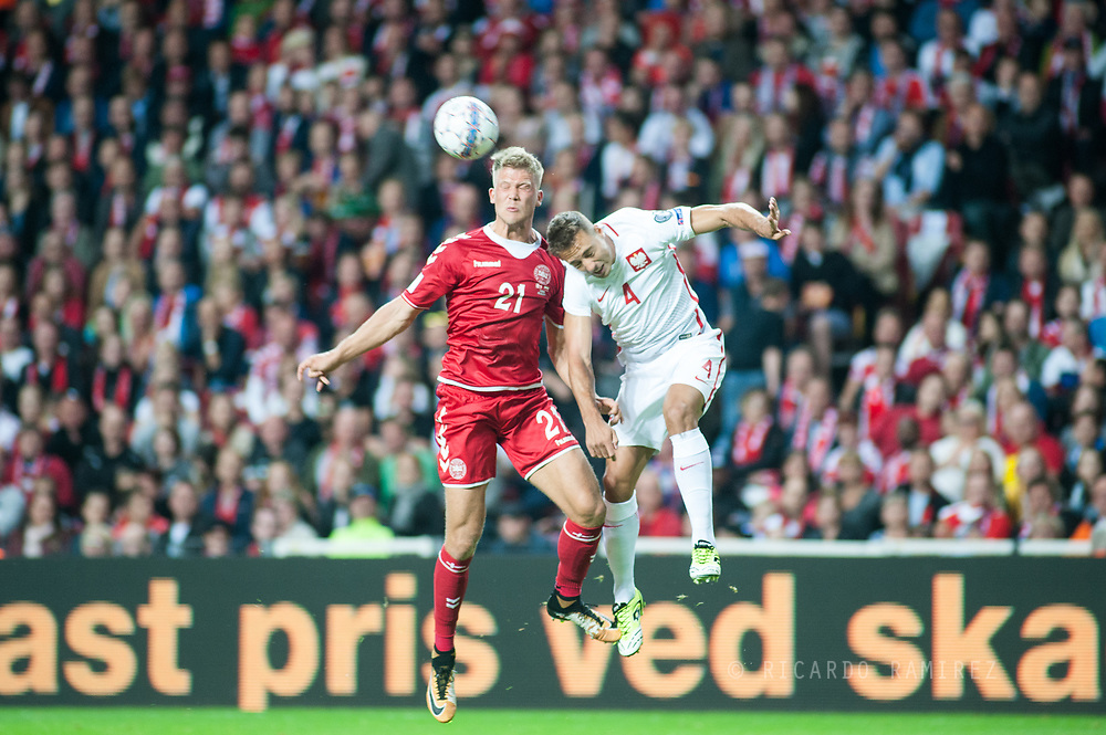 01.09.2017. Copenhagen, Denmark. <br /> Andreas Cornelius (21) of Denmark fights for the ball with Thiago Cionek (4) of Poland during the FIFA 2018 World Cup Qualifier between Denmark and Poland at Parken Stadion.<br /> Photo: © Ricardo Ramirez.