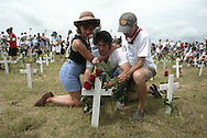a man is overcome by emotion after placing a flower on a crosst at Camp Casey II