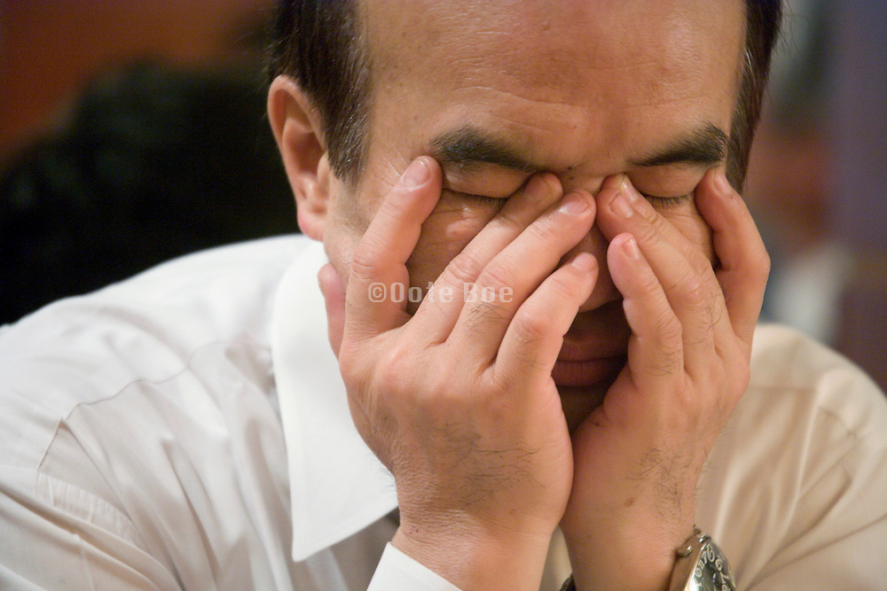 businessman holding his hands in front of his face