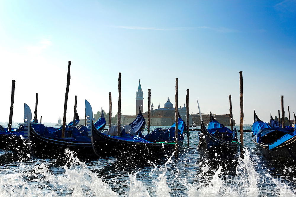 Gondolas and water splashes on Grand Canal in Venice, Italy. Church of San Giorgio Maggiore behind.