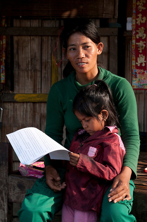 "The last light of day trickles in over the Cardomon Mountains highlighting Sokhon's smile.  She sits down with Sreymao who is busy studying her 2nd grade schoolwork.  Sokhon says, ""I want her to be a doctor, but we are too poor for that.  I hope she can be a nurse.""..Standing behind them, far enough away that he can't hear is, (need name), Sokhon's new husband.  Sokhon says:  ""My husband gives me good support. I cannot find another man better than him.  He doesn't drink and helps with the house work.  He carries water from the river.  He is responsible and takes Sreymao to school.  All my hope came back to me.  So I opened my heart back up.  Yes - I am in love"".   ."