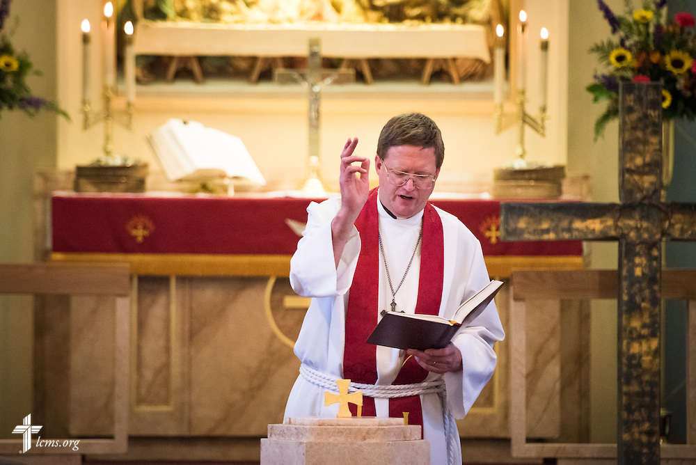 "The Rev. Timothy Mueller, pastor of St. John's Lutheran Church, rededicates the baptismal font on Sunday, August 9, 2015, during a ""Day of Thanksgiving and Rededication""  at the church in New Minden, Ill. Nearly two years ago, a tornado damaged the church and surrounding homes. LCMS Communications/Erik M. Lunsford"