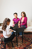 Mother and grandmother listening to young girl performing on toy piano.