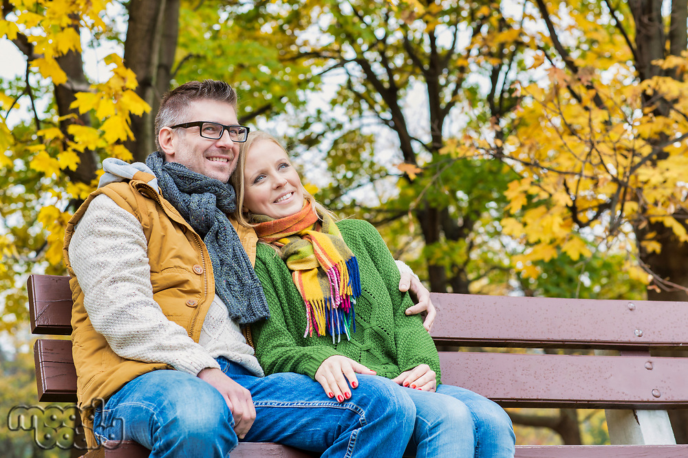 Portrait of mature couple sitting on bench while enjoying autumn in park