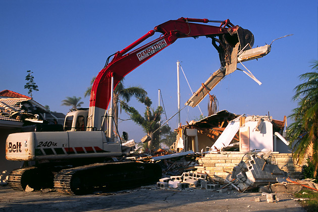 house being demolished by large equipment; Florida