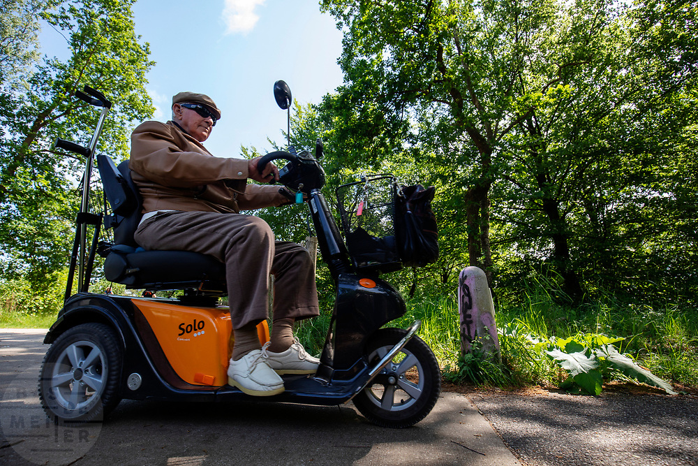 Een man in een scootmobiel rijdt over een fietspad in de bossen tussen Soest en Den Dolder.<br /> <br /> A man on a scooter rides at the cycle path between Soest and Den Dolder