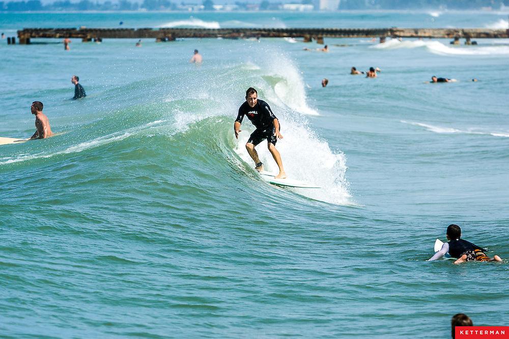 Surfers in Bradenton Beach, Florida take advantage of the leftover surf from Hurricane Gustav.