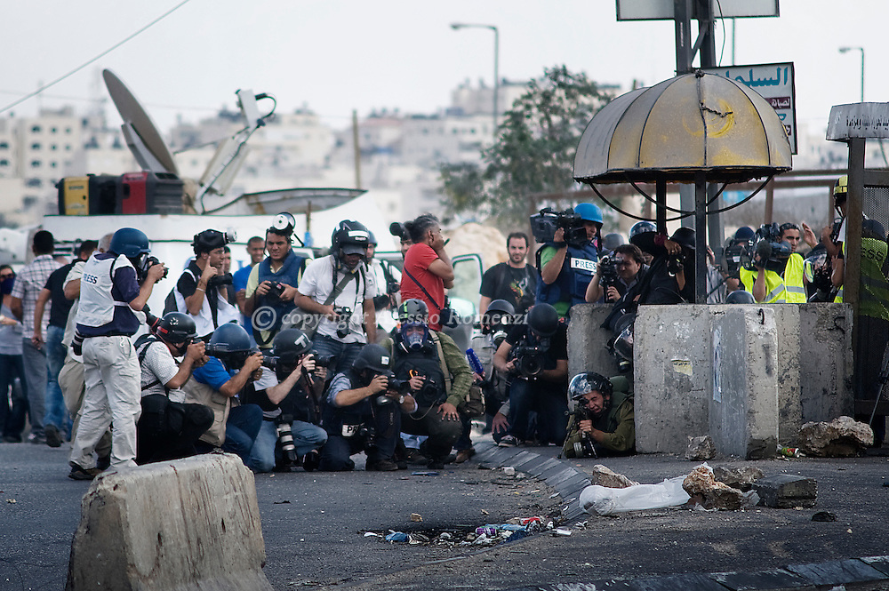 QALANDIA : Israeli soldiers take positions during clashes with Palestinian demonstrators, not seen, as photographers take pictures at the Qalandia checkpoint between the West Bank city of Ramallah and Jerusalem, Friday, Sept. 23, 2011, just hours before the Palestinian president, Mahmoud Abbas, was to deliver his widely anticipated request to the UN.  ALESSIO ROMENZI
