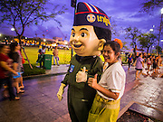 "24 JULY 2014 - BANGKOK, THAILAND: A woman poses for a selfie with a Thai military mascot character at the happiness party in Bangkok. The Thai Junta is organizing a series of public events throughout Thailand meant to bolster public opinion. The events are called ""restoring happiness to the people"" parties. They feature historic pageants, music, food, health checks and free haircuts. The party in Bangkok is on Sanam Luang, the Royal Parade Ground, which is near the Grand Palace and the Ministry of Defense.    PHOTO BY JACK KURTZ"