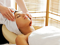 Young woman receiving facial massage, eyes closed