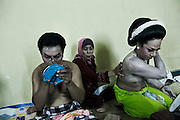 Mba Win applies white powder over her body helped by friend during the preparation for the show in Mojokerto, East Java, Indonesia, June 7, 2015.