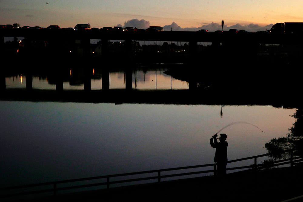 Tee Men fishes off East 8th Street next to the Peralta Colleges headquarters on Friday, Nov. 10, 2017, in Oakland, Calif. The Oakland A's are proposing a new stadium at the Peralta Community College District headquarters near Laney College. Cars on Interstate 880 are seen in the background.