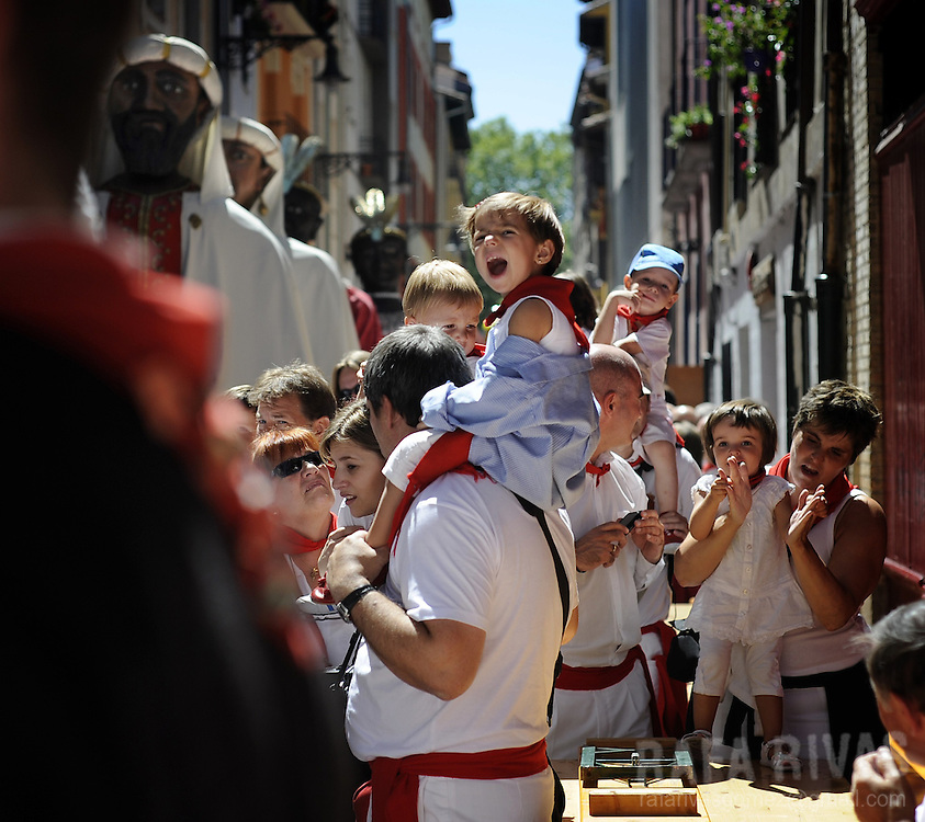Parents and children attend the Gigantes and Cabezudos (giant and large head puppets) parade, in a street of the the Northern Spanish city of Pamplona during the San Fermin festival, on July 12, 2012. PHOTO / Rafa Rivas