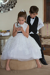 little girl and boy looking at a cell phone at a wedding