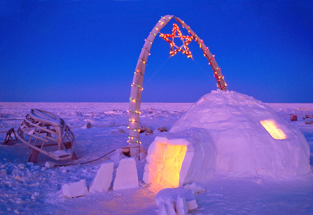 Alaska . Barrow . Igloo and whale bones adorned with christmas lights .