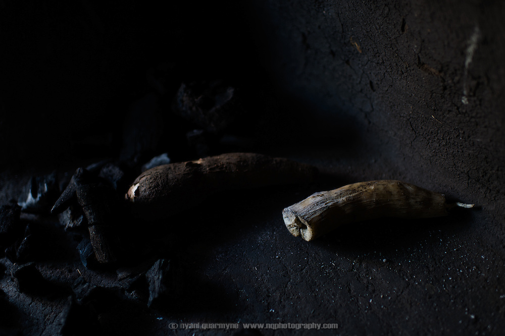 Cassava next to the hearth at the home of Regina Iyom in Imurok Payam in Eastern Equatoria, South Sudan on 9 August 2014. After being boiled the cassava will be sold at the small village market, and any proceeds used to support Regina and her son. Regina's husband is a government soldier, and has been away for about a year. Having come to her current home after having had to flee fighting in Juba in December 2013, she says she receives no support from him—locals say that soldiers frequently go unpaid for long periods of time. Facing acute food insecurity, Regina received seed to plant from Plan International.