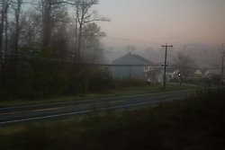 A suburban road running parallel to Amtrak rails, shot aboard the train.